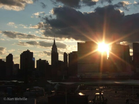 Dramatic sunset over Manhattan buildings seen from the Long Island City bank.