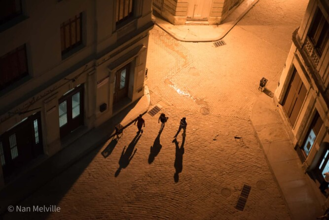 Looking down onto people walking - and their shadows - the late night Plaza de San Francisco de Asís square from the museum, Havana, Cuba.