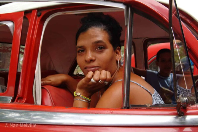 Lady in red vintage taxi, Cuba
